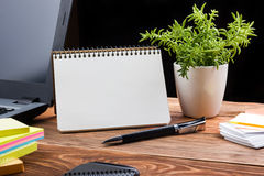 Office table desk with supplies, white blank note pad, cup, pen, pc, crumpled paper, flower on wooden background. Top Royalty Free Stock Image