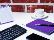 Office table desk. Workspace with note book, keyboard, office supplies and coffee cup on white background.  royalty free stock image