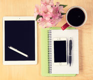 Office table with digital tablet, smartphone, reading glasses and cup of coffee stock image