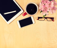 Office table with digital tablet, smartphone, reading glasses and cup of coffee. View from above Stock Photos