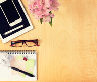 Office table with digital tablet, smartphone, reading glasses and notepad. View from above Stock Image