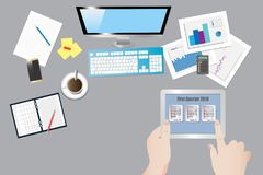 Office table with equipment top view. Top view of the office desk with office equipment. Hands are holding the tablet and the finger point to a  screen with Royalty Free Stock Image