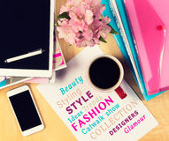 Office table with fashion magazines, digital tablet, smartphone and cup of coffee. View from above. With copy space Royalty Free Stock Image