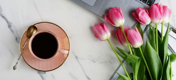 Office table feminine desk. Top view office table feminine desk. workspace with laptop, cup of cofee and bouquet pink tulip Royalty Free Stock Photo