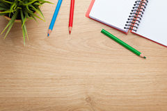 Office table with flower, blank notepad and colorful pencils Royalty Free Stock Images