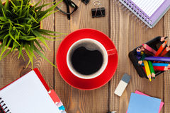 Office table with flower, supplies and coffee cup Royalty Free Stock Photo