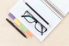 Office table with glasses over notepad, pen and pencil Royalty Free Stock Photos