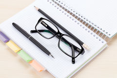 Office table with glasses over notepad, pen and pencil Stock Images