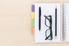 Office table with glasses over notepad, pen and pencil Royalty Free Stock Image