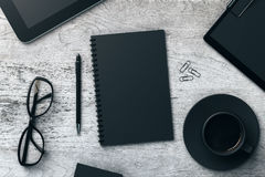 Office table with items. Top view of aged wooden office table with black notepad, coffee cup, pen, glasses, clips, tablets and other items. Workplace concept Royalty Free Stock Photography