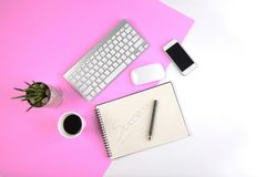 Office table with keyboard, mouse, notebook and smartphone on modern two tone white and pink background Stock Photo