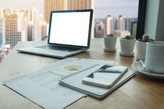 Office table with laptop blank screen computer building background stock image