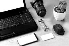 Office table with laptop computer, camera lens, smartphone, eyeg Royalty Free Stock Images