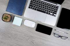 Office table with laptop computer, notebook, digital tablet, pen, smartphone, mouse, eyeglasses and coffee on wood background. Office table with laptop computer Stock Photos