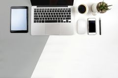 Office table with  laptop computer, notebook, digital tablet and smartphone on modern two tone white and grey background Royalty Free Stock Photo