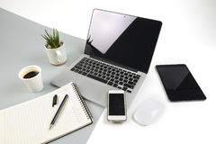 Office table with laptop computer, notebook, digital tablet and smartphone on modern two tone white and grey background.  royalty free stock images