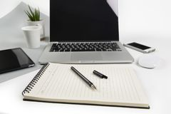 Office table with  laptop computer, notebook, digital tablet and smartphone on modern two tone white and grey background Stock Images
