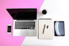 Office table with  laptop computer, notebook, digital tablet and smartphone on modern two tone white and pink background Stock Images
