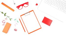 Office table with Laptop, Red Notebook, Clipboard, Clips and Flo. Wer. Top view with copy space Stock Image