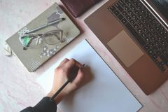 Office table with laptpo, notebook, pen, pencil, glasses, wallet and white paper. stock photo