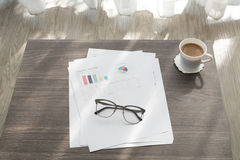 Office table with modern glasses on business report chart paper Royalty Free Stock Images