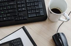 Office table with notebook keyboard mouse and coffee Royalty Free Stock Image