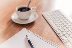 Office table with notepad, computer keyboard and coffee cup  and Stock Photos