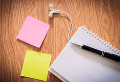 Office table with notepad, pen , headphone, sticky notes Royalty Free Stock Photo