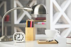 Office table with objects. Close up of office table with book, coffee cup, supplies and other objects. Occupation, morning, leisure, knowledge and information Stock Image
