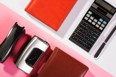 Office table with pen, calculator. Colour. Flat lay top view royalty free stock photography