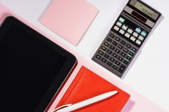 Office table with pen, calculator. Colour. Flat lay top view royalty free stock images