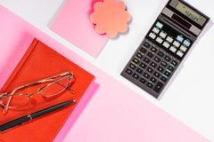 Office table with pen, calculator. Colour. Flat lay top view stock images