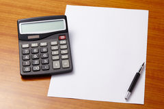 Office table with pen, calculator and empty paper Stock Photography