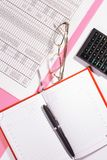 Office table with pen, calculator and glasses. Colour. Flat lay top view royalty free stock photography