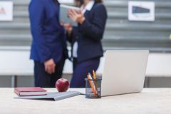 On the office table, an apple, a laptop, a notepad folder and pens. In the background, office workers. royalty free stock images