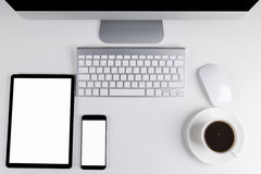 Office table with tablet computer and smartphone, wireless computer keyboard and mouse, cup of coffee, copy space notebook. empty Royalty Free Stock Photo