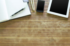Office table with tablet, pen on notebook, smartphone on old woo Royalty Free Stock Photography