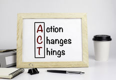 Office table with wooden frame with text - Action Changes Things Stock Image