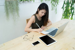 Office table with young asian woman writing on notepad paper, As Royalty Free Stock Photography