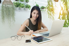 Office table with young women in smiling face and writing on not Royalty Free Stock Photography