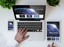 Office tabletop earth responsive design website. Office tabletop with tablet, smartphone and laptop showing earth responsive design website. Some elements Royalty Free Stock Images