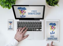 Office tabletop free download. Office tabletop with tablet, smartphone and laptop showing free download website. All screen graphics are made up royalty free stock image