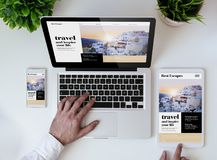 Office tabletop travel responsive design website. Office tabletop with tablet, smartphone and laptop showing travel responsive design website Stock Photography