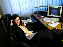 Office talk 1. Young woman relaxing and discussing over the phone stock image