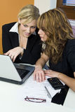 Office Teamwork. Two attractive young female executives working together on a laptop royalty free stock images