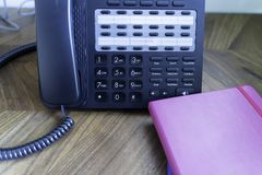 Office Telephone console on wood table with notebooks royalty free stock photography
