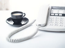 Office telephone and cup. Modernwhite business office telephone and cup Stock Image
