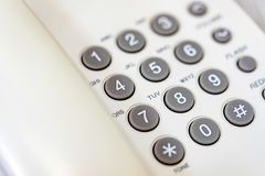 Office telephone keypad close. Close up white landline phone with grey buttons Stock Image