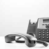 Office telephone. Office landline telephone with handset off the base on a white table Stock Photography