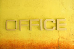 Office text sign on yellow grunge cement wall Royalty Free Stock Photos